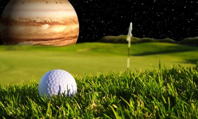 a golf ball behind Jupiter showing size comparison